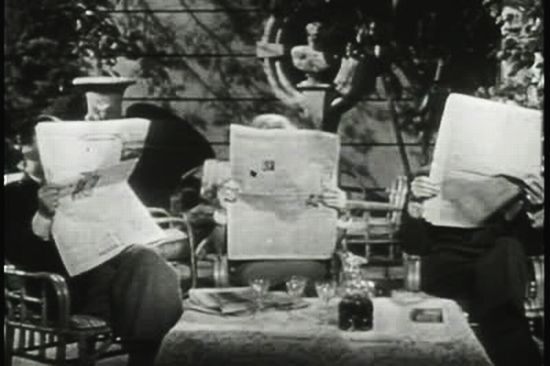 stock-footage-three-people-reading-newspapers-at-table (1)